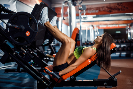 Woman doing fitness training on a leg extension push machine with weights in a gym Standard-Bild
