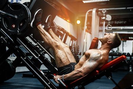 フィットネスクラブでプレス機を使用している男性。シミュレーターで足の体操をしている強い男。側面図 写真素材