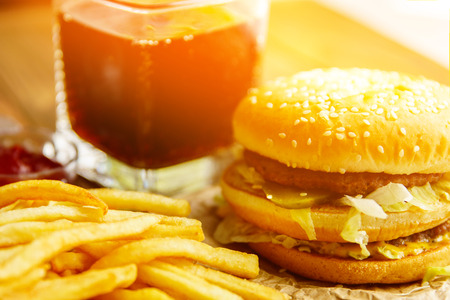 Burger on craft paper with fries and soda pop on wooden table. Sun Flare
