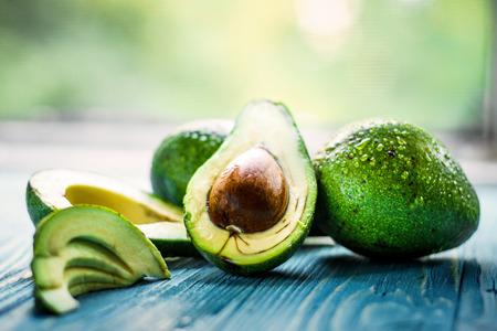 Fresh Green Avocado on blue wooden background. Stock Photo
