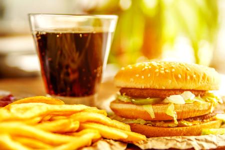 Hamburger op ambachtpapier met frieten en frisdrank op houten tafel. Zonnevlam