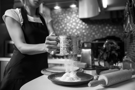 Woman sifting flour through sieve In the kitchen. Selective focus. Stock Photo