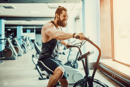 Man using exercise bike at the gym. Fitness male using air bike for cardio workout at Functional training gym.