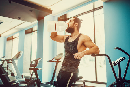 very power athletic bearded guy relaxing after workout and hold or drink water from big bottle in gym