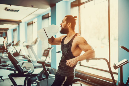 traction: very power athletic bearded guy relaxing after workout and hold or drink water from big bottle in gym