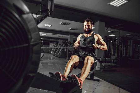 Bebaarde gespierde man Ssing roeimachine op functionele training gym