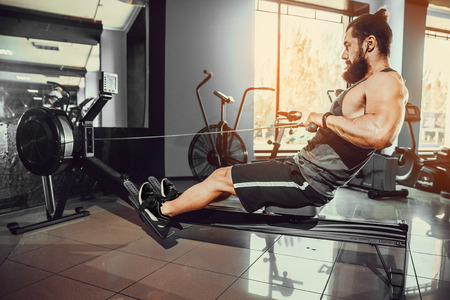 Bearded Muscular Fit Man Ssing Rowing Machine at Functional Training Gym Stock Photo