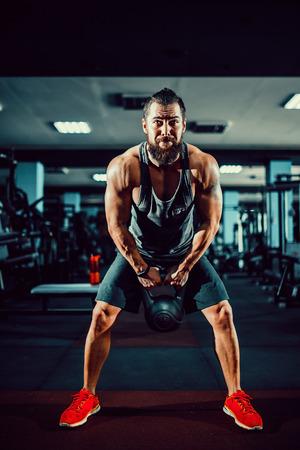 フィットネスケトルベルスイング練習ひげ男ジムでのトレーニング 写真素材