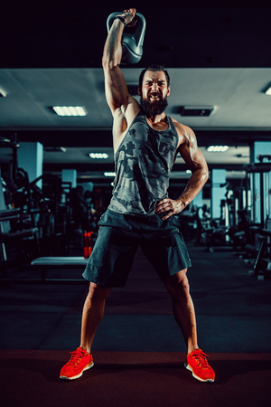 Fitness Kettlebells swing exercise bearded man workout at gym Banco de Imagens