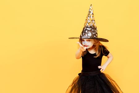 작은 소녀 할로윈 마녀 드레스와 모자 무서 워 하 고 카메라에 손가락을 가리키는 동안 얼굴을 만들기. 노란색 배경에 격리.