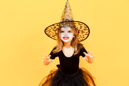 Small girl in Halloween witch dress and hat scaring and making faces isolated  on yellow background 34c239a22e97