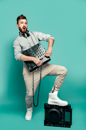 Young trendy male posing with portable mixing console and looking at camera on green isolated studio background.