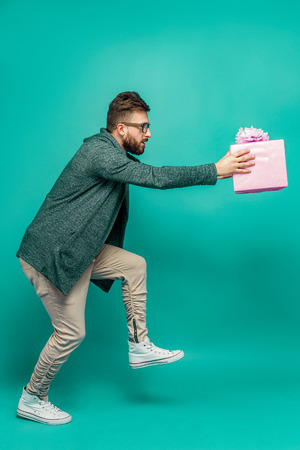 Young man in casual clothing creeping secretly with pink gift box in hand isolated on green studio background. Christmas concept.