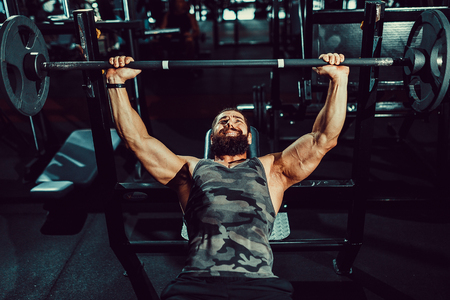 Very Strong bearded man doing bench press workout in gym Stock Photo