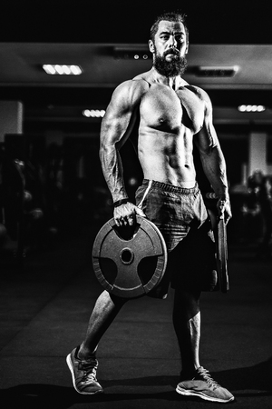 Athlete muscular bearded bodybuilder man with naked torso posing with dumbbells in gym.