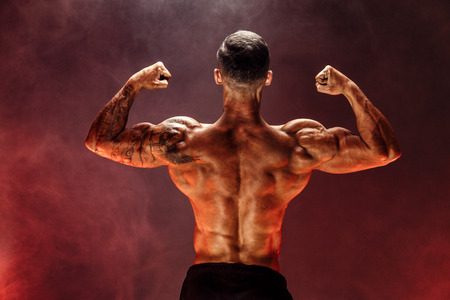Bodybuilder Performing Rear Double Biceps Pose In Studio. Background with red smoke.
