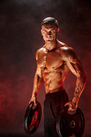 Very brawny guy bodybuilder. Bodybuilder with dumbbells in his arms on dark background with red smoke.
