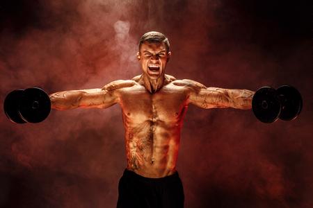 sehr muskulöser Kerl Bodybuilder, führen Sie Übung mit Hanteln, auf Deltamuskelschulter aus. Sream für die Motivation. Geschossen auf rotem Rauchhintergrund des Studios.