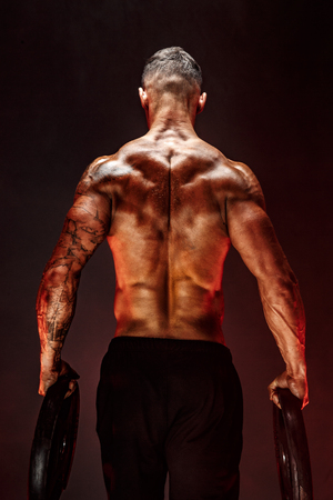The back view of torso of attractive male body builder with dumbbells on dark smoky background.