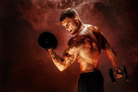 Very brawny guy bodybuilder. Portrait of roaring muscular man lifting dumbbell in red smoke. Studio shot. Banco de Imagens - 87232269