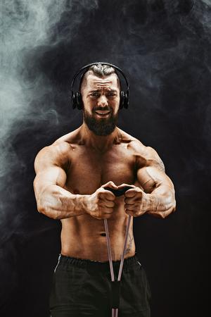 フィットネス スタジオでのバンドのストレッチ運動のヘッドフォンで男。弾性ゴムバンド運動筋肉スポーツ男。フィット、フィットネス、運動、エ