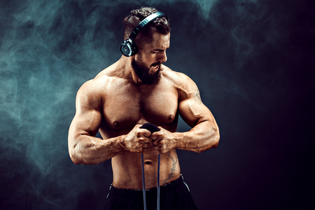 Człowiek fitness w słuchawkach ćwiczeń z rozciąganiem w studio. Mę żczyzna sportowy mę żczyzna korzystania z elastycznej gumki. Fit, fitness, ćwiczenia, trening i zdrowy tryb życia
