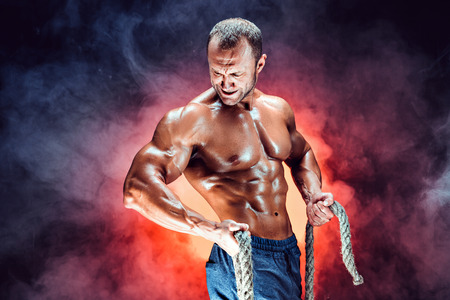 Strong shirtless bodybuilder man working out hard with rope. Stockfoto
