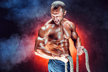 Strong shirtless bodybuilder man working out hard with rope. Фото со стока