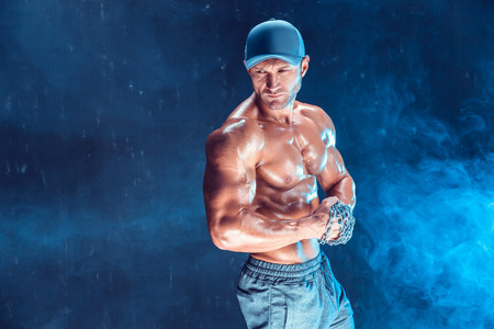 Serious muscular fighter in cap with the chains braided over his fist in smoke Stock Photo