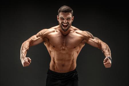 Culturista molto muscoloso ragazzo in posa. Bello potere maschile ragazzo sportivo. Fitness uomo muscoloso. Ruggito
