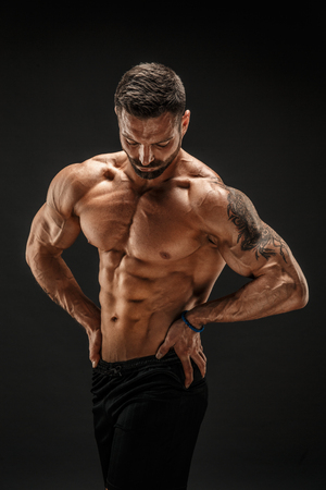 Very brawny guy bodybuilder posing. Beautiful sporty guy male power. Fitness muscled man. Archivio Fotografico
