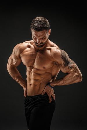 Zeer gespierde man bodybuilder poseren. Mooie sportieve kerel mannelijke macht. Fitness gespierde man. Stockfoto