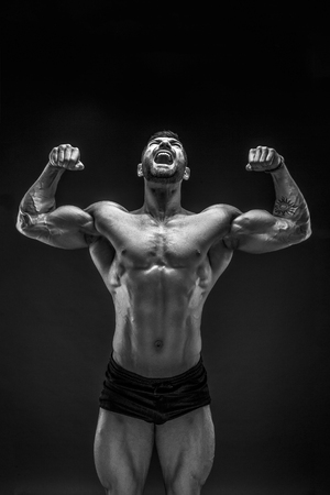 Handsome muscular shirtless man screaming and looking up isolated on black.