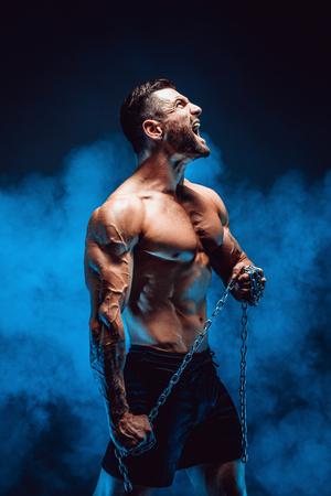 비명과 체인을 들고 shirtless 근육 질의 남자의 측면보기.