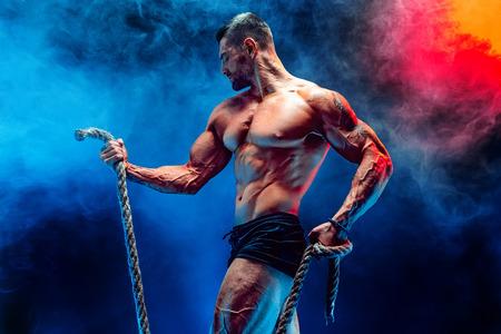 Vista lateral del hombre muscular del culturista que entrena difícilmente con la cuerda en estudio, humo. Foto de archivo - 87755637