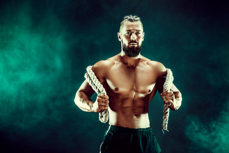 Muscular bearded bodybuilder man Posing with rope in studio.