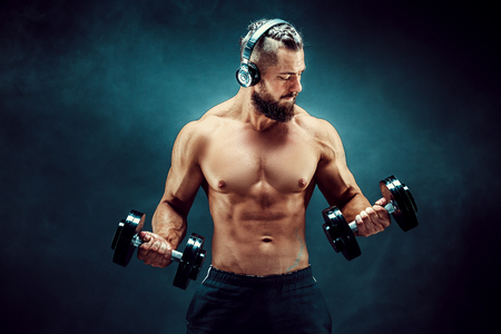 Athletic man training muscles with dumbbells in studio on dark background. Strong bodybuilder with six pack, perfect abs, shoulders, biceps, triceps and chest posing with headphones