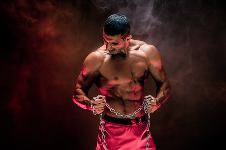 Portrait of muscular sportsman tearing metal chain.Black background with red smoke