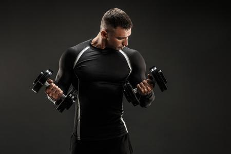 ハンサムなボディービルダーの男性ダンベルで上腕二頭筋の運動を行います。スタジオ撮影します。