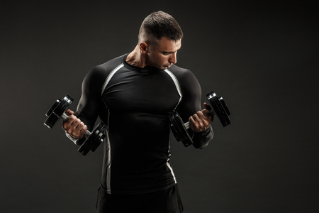 Handsome bodybuilder man doing exercise on biceps with dumbbell. Studio shot. Stock Photo