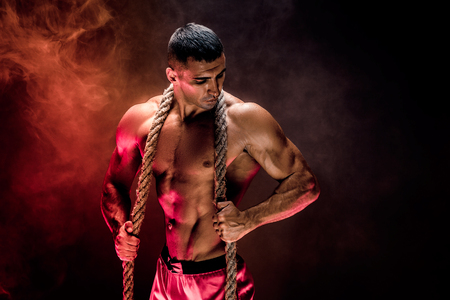 Strong shirtless bodybuilder man working out hard with rope. Archivio Fotografico