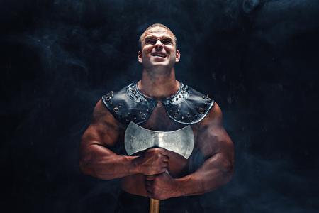 도끼로 포즈를 취하는 근육 고대 전사 남자의 스튜디오 샷. 스톡 콘텐츠