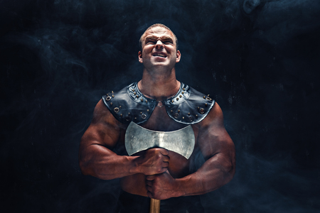 Studio shot of muscular ancient warrior man posing with axe. Stock Photo