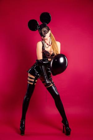 검은 가죽 드레스와 빨간 풍선 검은 풍선 마스크에서 포즈를 취하는 젊은 여자. 스톡 콘텐츠