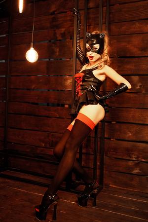Young model wearing costume of cat posing sensually in studio.