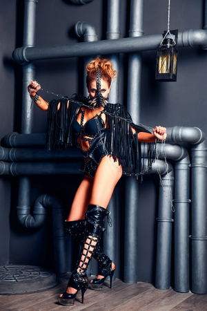 Young attractive woman wearing seductive leather outfit and high heels posing aggressively with chain.