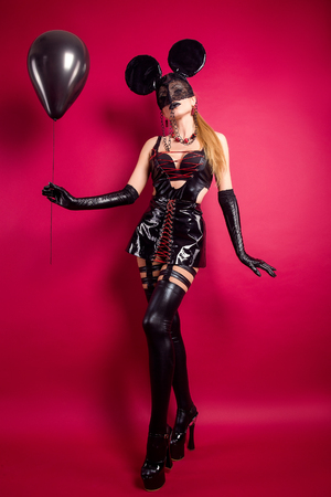 Young woman in black leather dress and high heels posing in mask with black balloon on red. Stock Photo