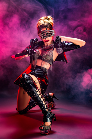 Young anonymous woman wearing alluring leather lingerie decorated with chains and rivets posing in studio.