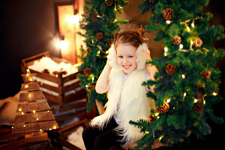 Cute little girl in fur earmuffs sitting near Christmas tree and cheerfully smiling.