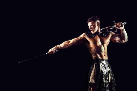 Ritratto di bel gladiatore muscolare con due spade. Studio girato Sfondo nero. Archivio Fotografico